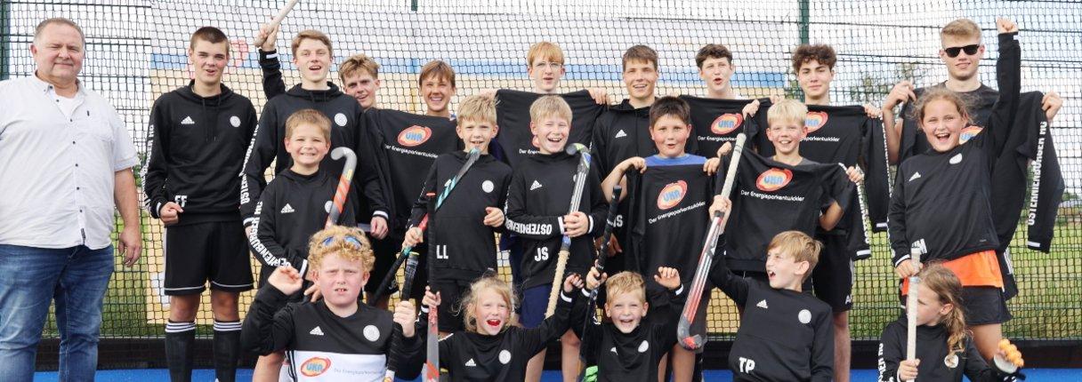 Spielerinnen und Spieler des Osternienburger Hockeyclubs Schwarz-Weiß präsentieren ihre neue von UKA gesponserte Ausrüstung