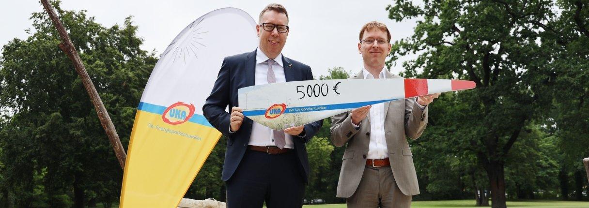 Daniel Peters (rechts) von UKA Cottbus überreicht Peter Albert von der Bürgerstiftung erneut eine Spende über 5.000 Euro für den Wasserspielplatz im Eliaspark.