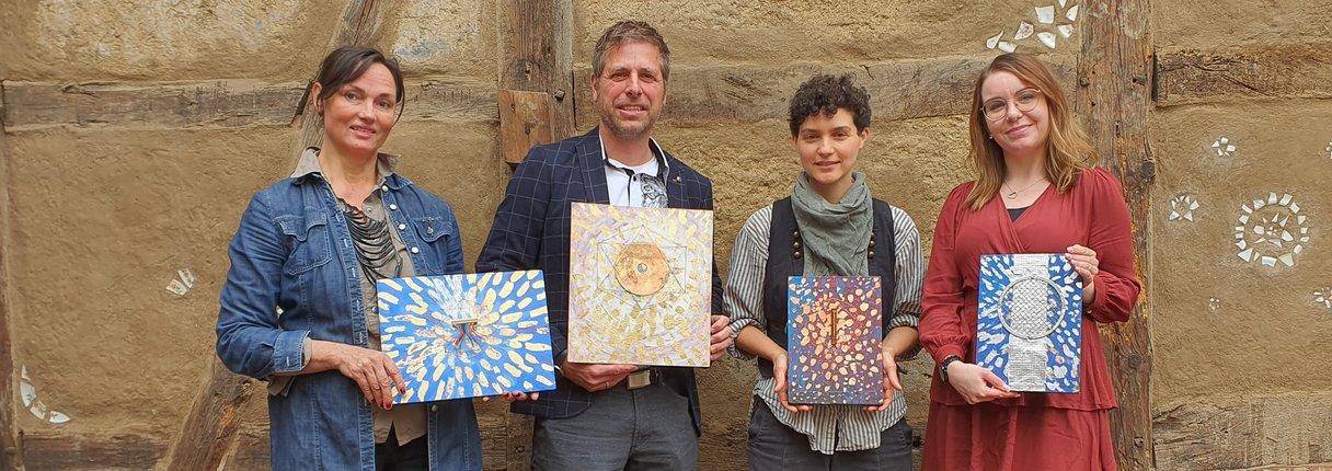 Die israelische Künstlerin Maayan Anavim (zweite von rechts) präsentiert ihre Upcycling-Kunstwerke in Lübz. Sie werden den Gewinnern eines Videowettbewerbs zum Thema Nachhaltigkeit neben den Geldpreisen als Trophäen überreicht. Die Werke präsentiert sie gemeinsam mit Julia Theek vom Zentrum für Zirkuläre Kunst, Martin Müller von UKA und Carola Riehl vom Lernen Aktiv e.V. (von links).