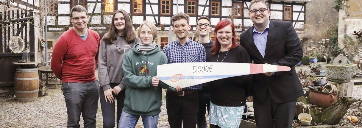 Benedikt Laubert von UKA (vierter von links) überreicht die Spende über 5.000 Euro an Vertreter des Flexiblen Jugendmanagements (von links): Maximilian Schikore-Pätz, Saskia Dürr, Nele Liebscher, Moritz Schneider, Marlen Linke und Robert Wölk.