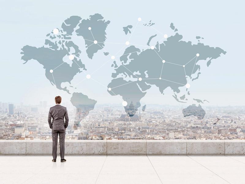 Geschäftsmann blickt auf Weltkarte.