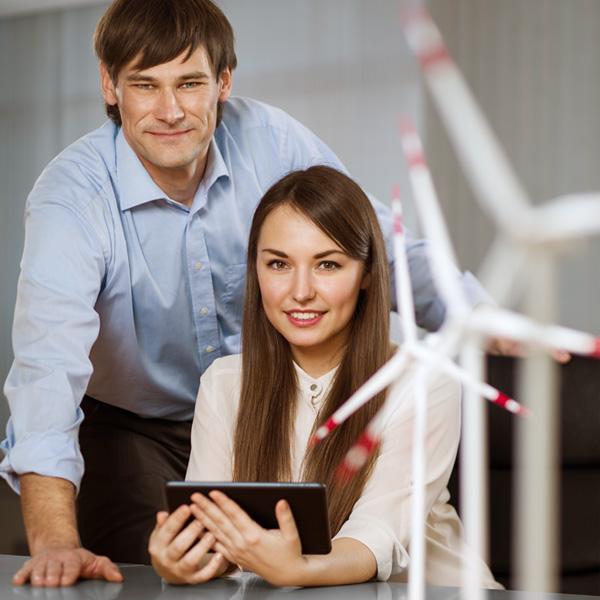 Frau und Mann sitzen/stehen an einem Schreibtisch mit Modellen von Windenergieanlagen.