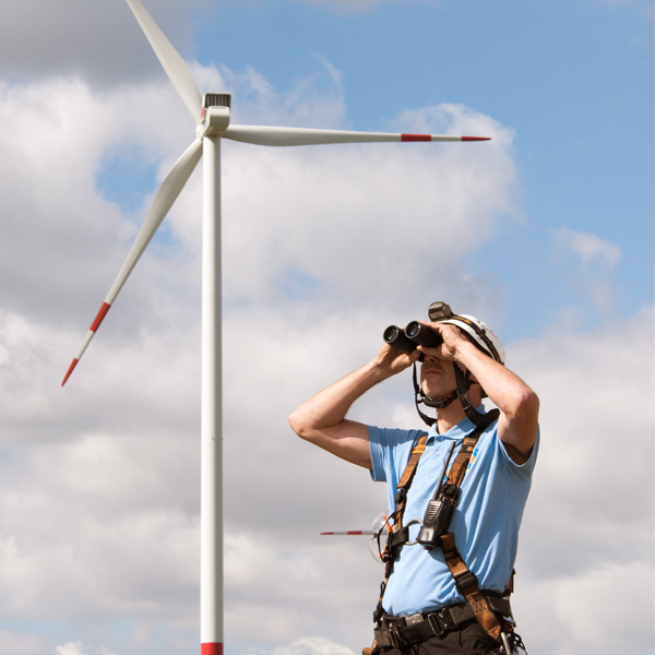 man looks through binoculars with wind power plants behind him